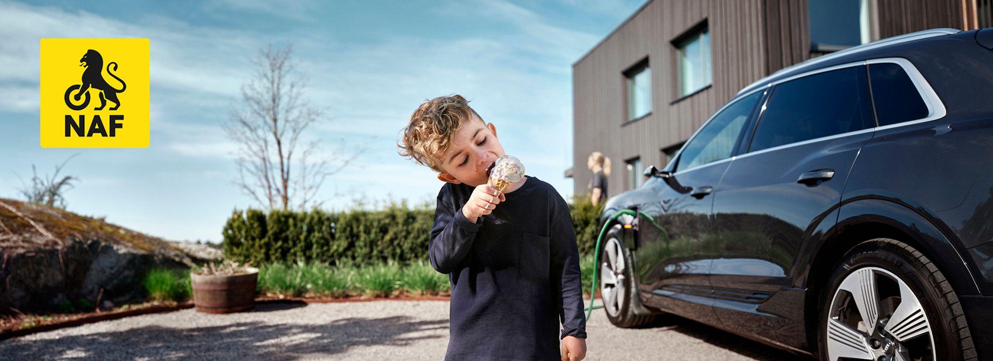 Illustrasjonsbilde av gutt som spiser is. I bakgrunnen ser man en elbil som står til lading.